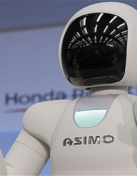 A white artificial intelligence robot holding two fingers up on each hand.